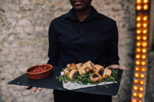 A server holds a board of Pieminister sausage rolls