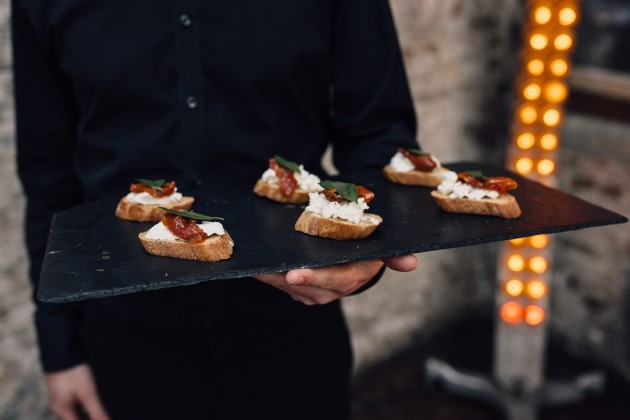 A server hold a platter of Pieminister canapes