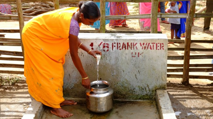 Woman collects water from a FRANK Water tap