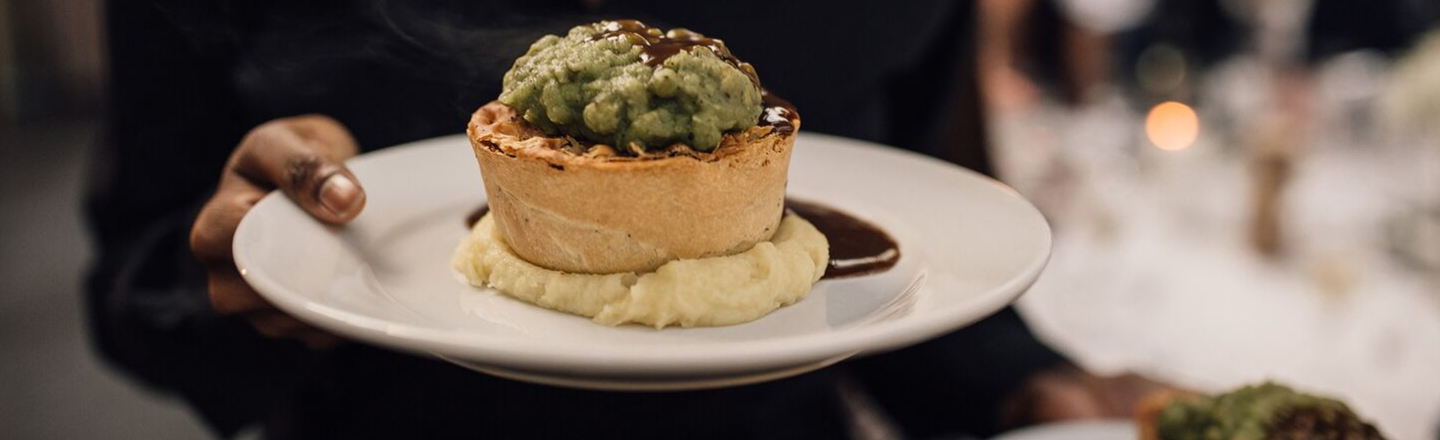 A server holds a Pieminister pie, mash and mushy peas on a plate